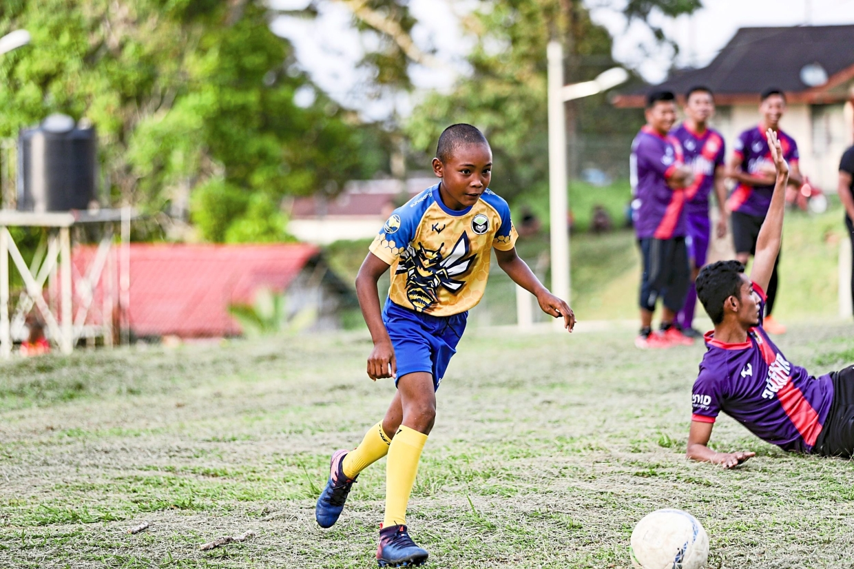 A player from The Botaks displaying his dribbling skills during the friendly match against Ohana FC who visited Kampung Lemoi.
