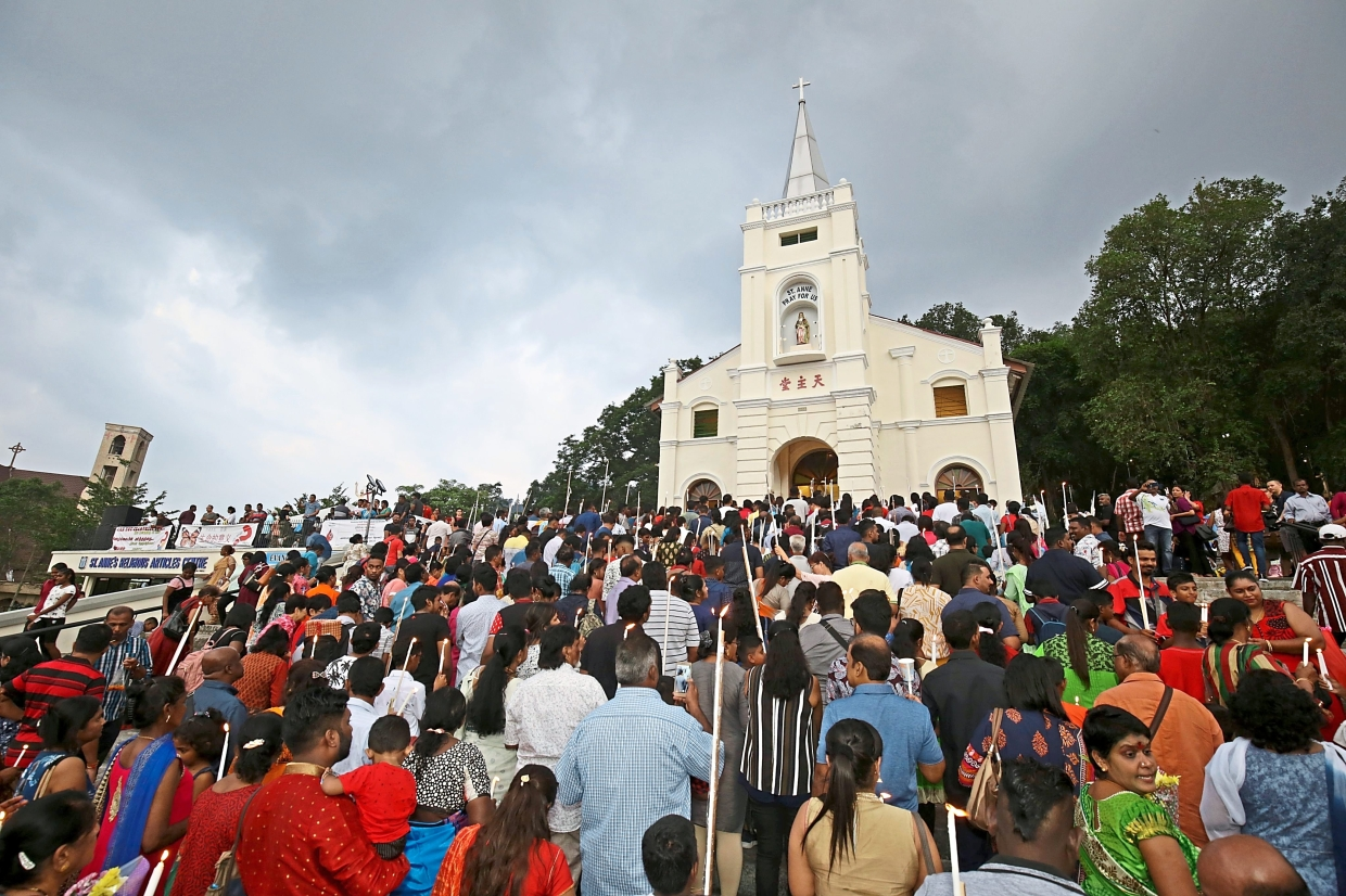 Worshippers surging forward to offer prayers during the St Anne's Feast despite overcast skies at St Anne's Church Bukit Mertajam.