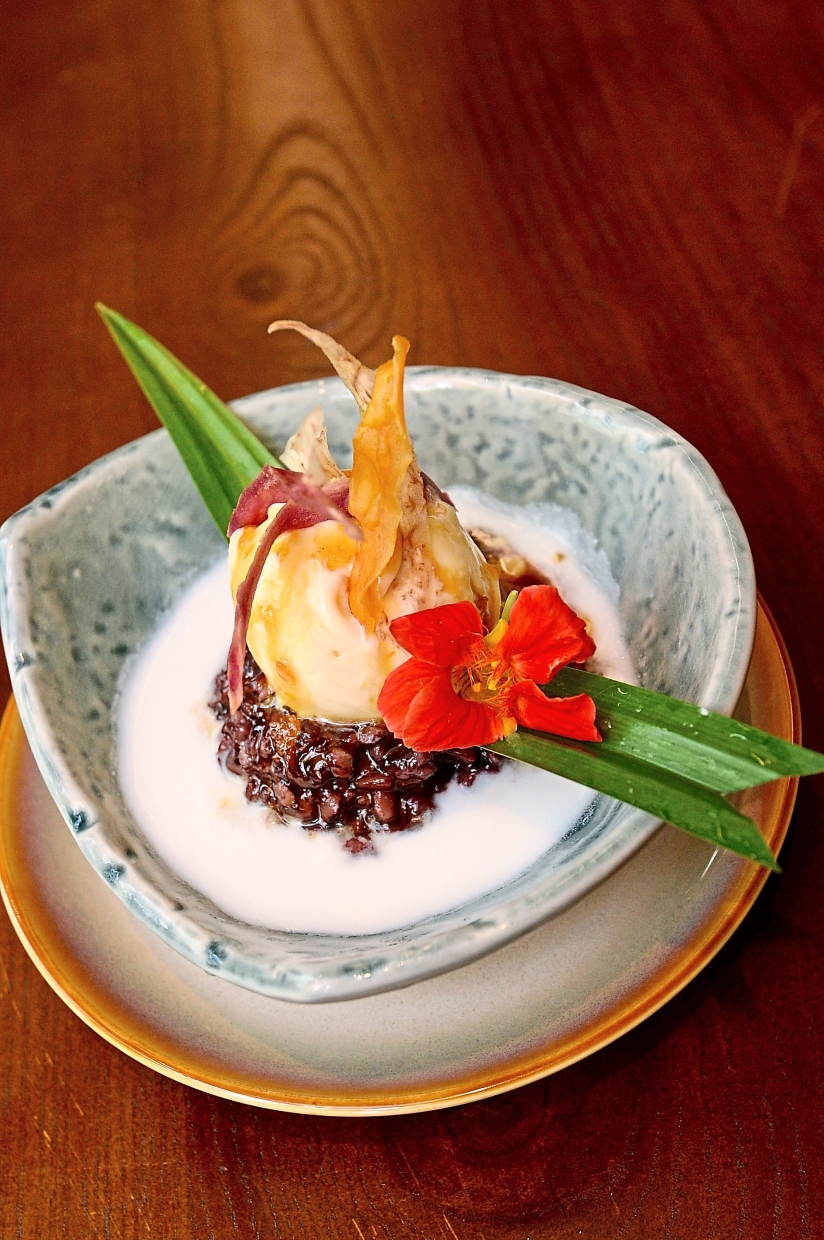The black glutinous rice porridge is topped with durian ice cream and garnished with yam and sweet potato.