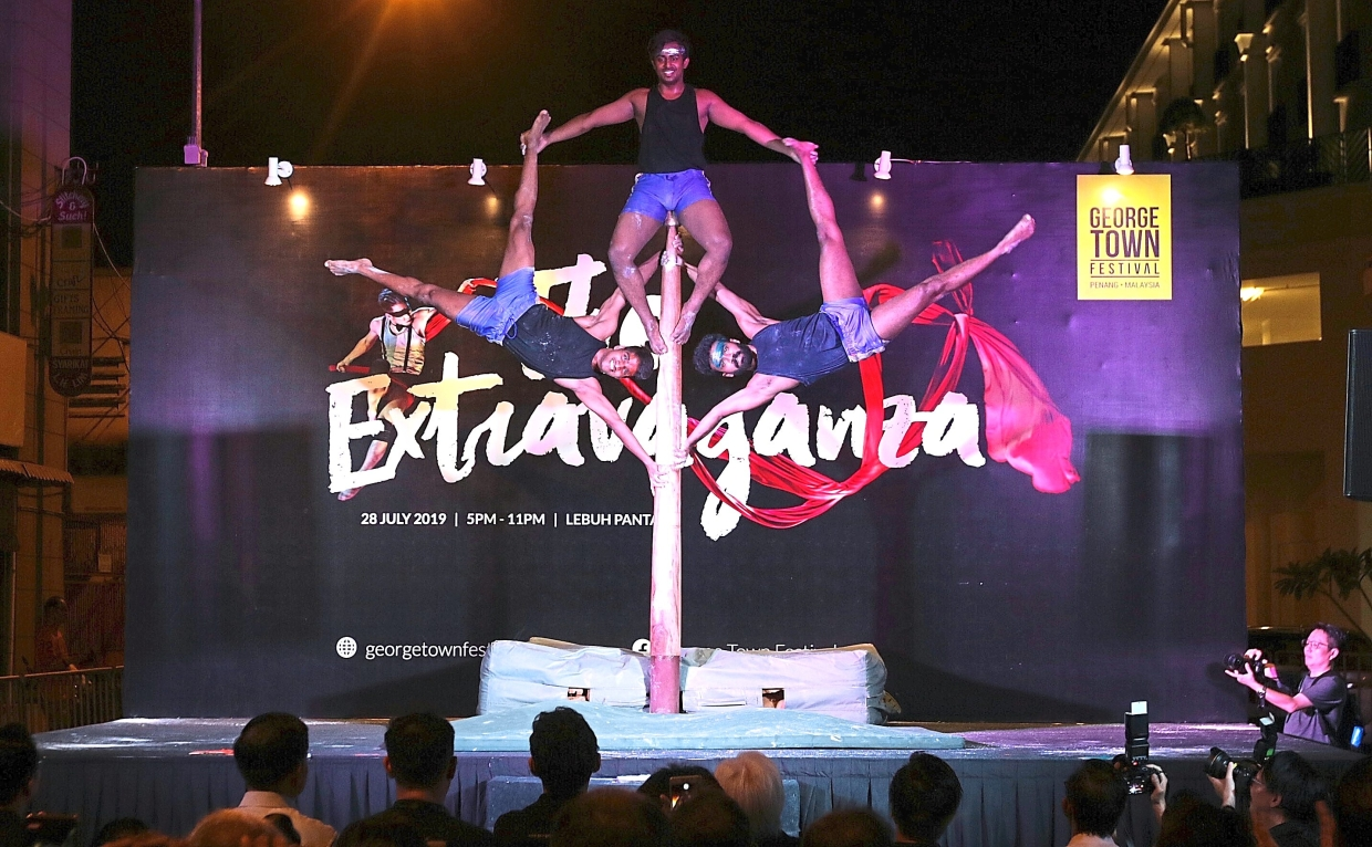 Gymnasts showing their balancing skills on a vertical wooden pole in the Mallakhamb performance from India.