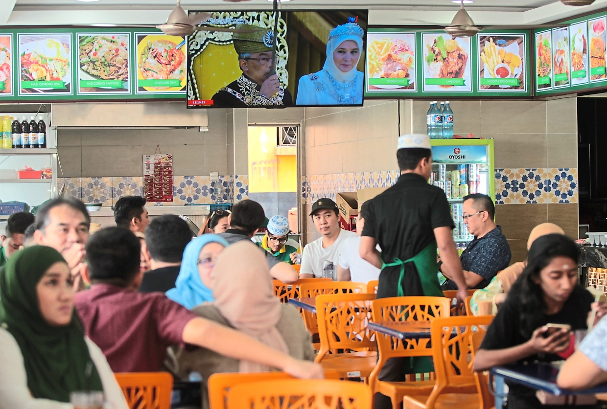 Customers at a mamak restaurant in Kelana Jaya watching the live telecast of the King's installation while having breakfast.