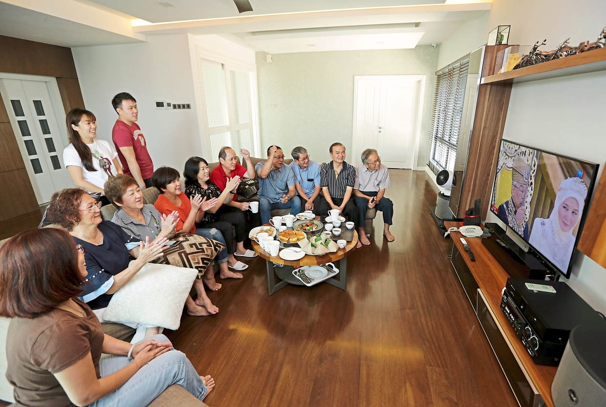 Taman Desa Residents Association committee members watching the King's installation ceremony on TV before starting their meeting.