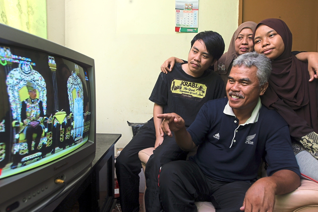 Abdul Razak (seated in the middle) with his family watching the live telecast. He said it was a chance to see all the state rulers gathered in one place.