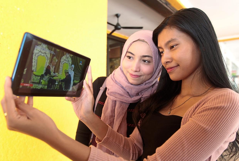 Amysha Rusdi (right) and Siti Syazwani Muhd Mansor watching the live streaming of the ceremony at a restaurant in Kelana Jaya.
