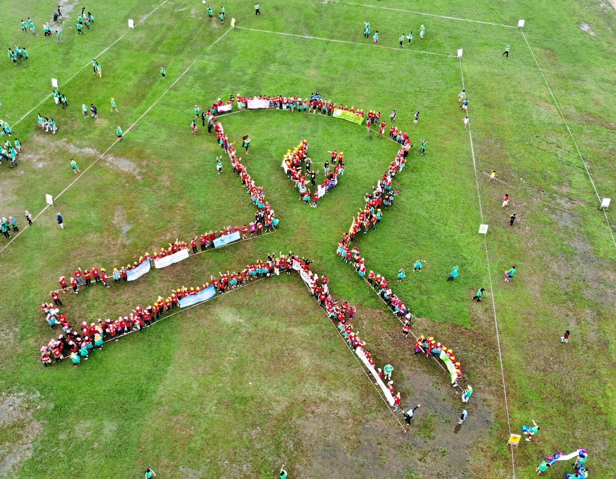 Cancer survivors dressed in red t-shirts forming a red ribbon in the middle of the field to signify their fight for cancer.