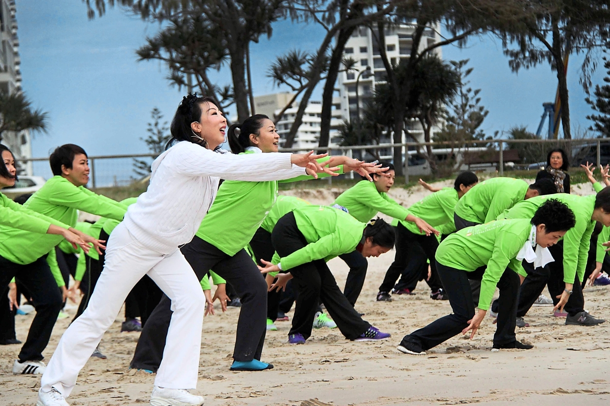 Bai (in white) teaching students the right qigong pose during a lesson.