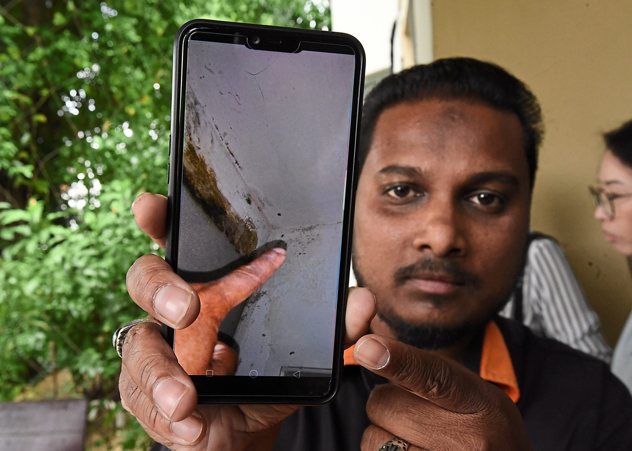 E-Garden house buyers Muhammad Hafiz Mohammed Yusoff 30, showing the leaking of his unit  during the press conference at CAP office in George Town yesterday. - Starpic by MUSTAFA AHMAD/The Star/31 July 2019