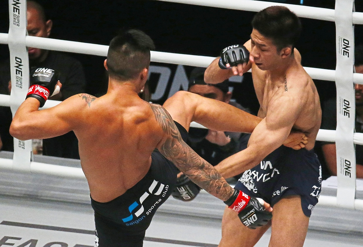 Nguyen (left) attacking challenger Koyomi Matsushima of Japan with a kick during their title fight.  Nguyen retained his title for the third time via a stoppage in the second round.