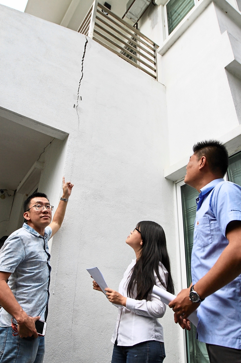 (From left) Tiew, Wong and So inspecting a cracked wall.