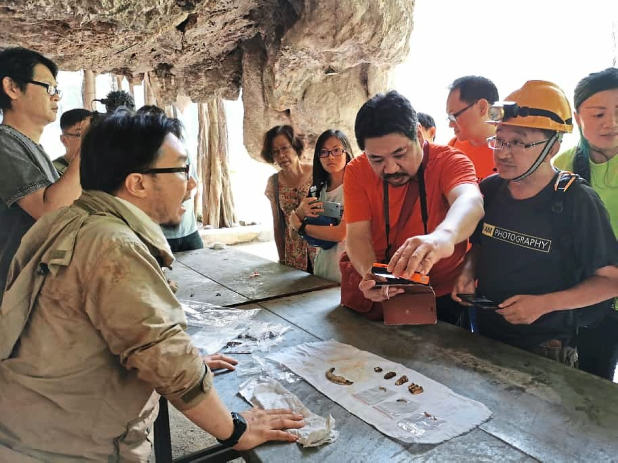 Participants having a closer look at some fossilised bones found by caving enthusiasts in Gunung Rapat, Ipoh.