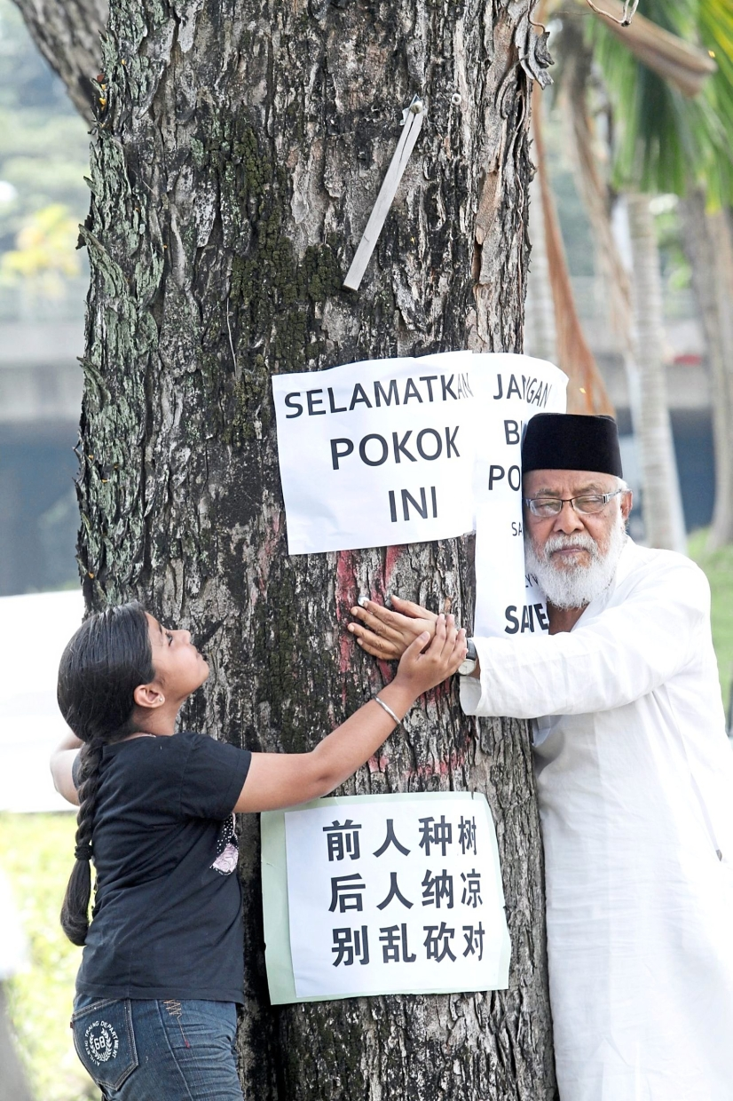 Mohamed Idris (right) and a CAP staff member's daughter, Komalpreet Kaur, hugging an angsana tree slated to be axed for a road-widening project back in 2012. In Penang, the tree-planting initiative to make the state green was attributed to Mohamed Idris. —filepic