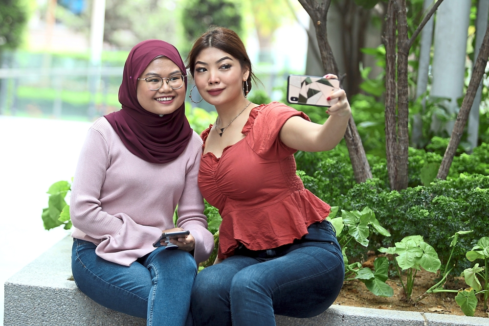Nur Izzaty (left) and Ku Munirah collectively have over 45,000 photos in their smartphones, mostly of themselves, their families and friends. — KAMARUL ARIFFIN/The Star