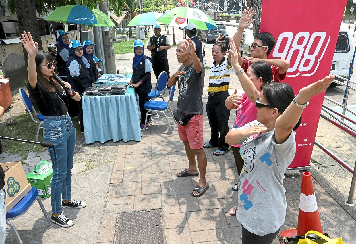 A crew member of 988FM interacting with passers-by during the promotional event.