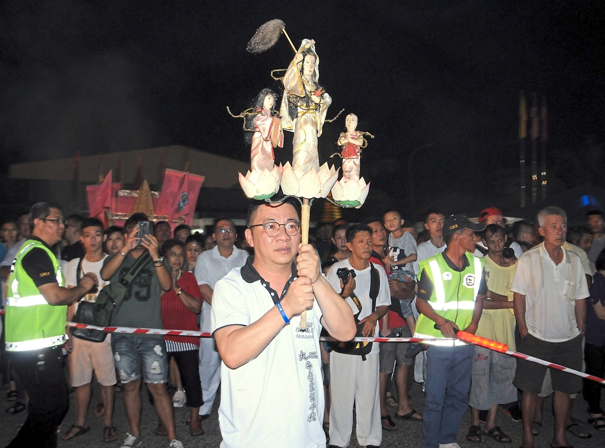 A  temple committee member holding figurines of three deities.