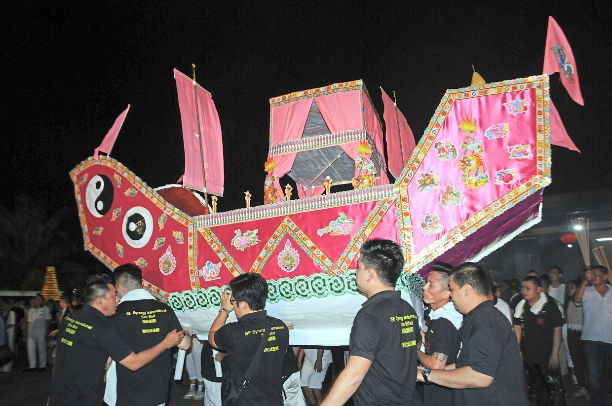A paper boat is carried out to be burnt along with the effigy.
