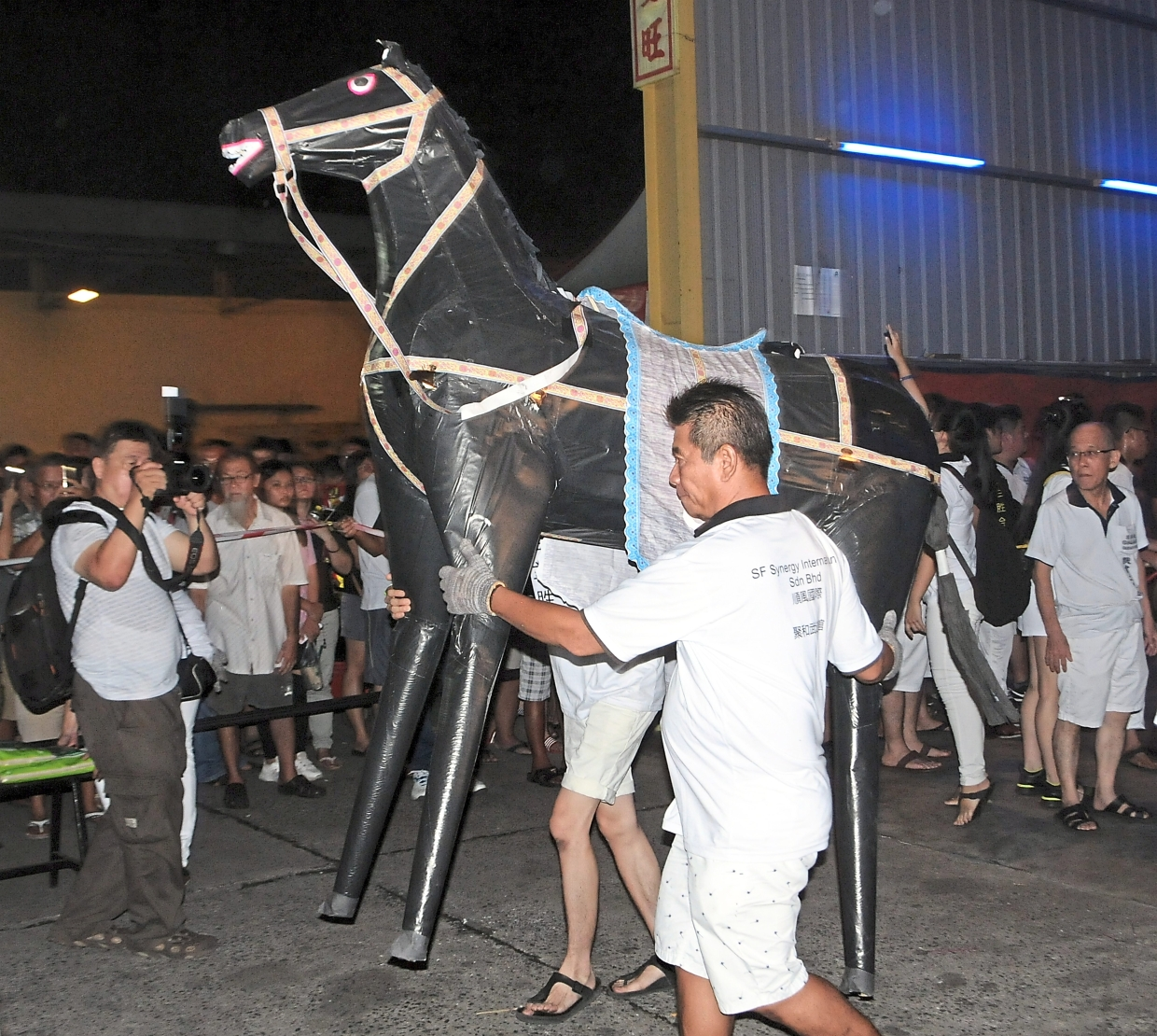 Two temple committee members carrying a paper effigy of a horse.
