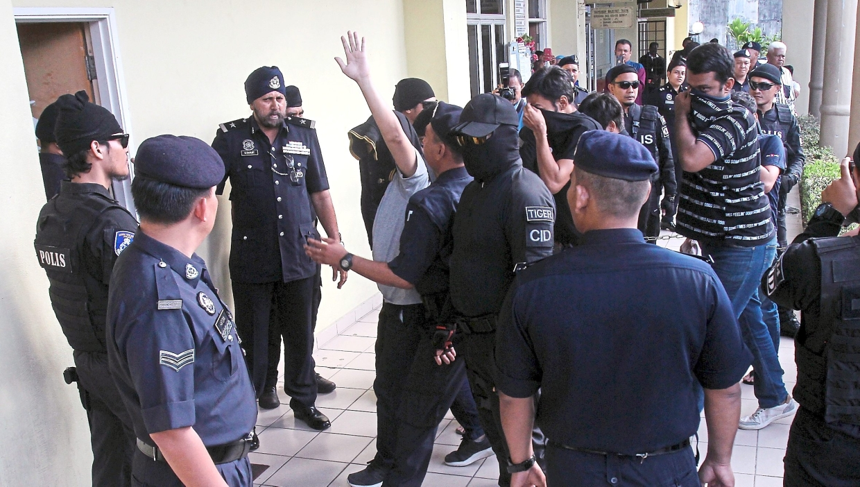 Tight security: The Emi Keju gang members being brought to the Sessions Court in Selayang.