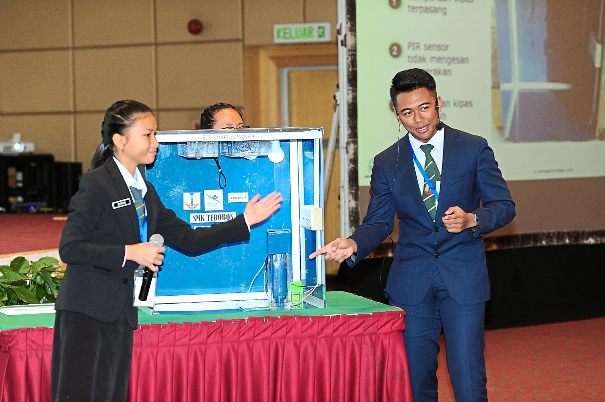 The first runners-up from SMK Tebobon, showcasing their Eco-Smart Classroom project to judges during the national finals.