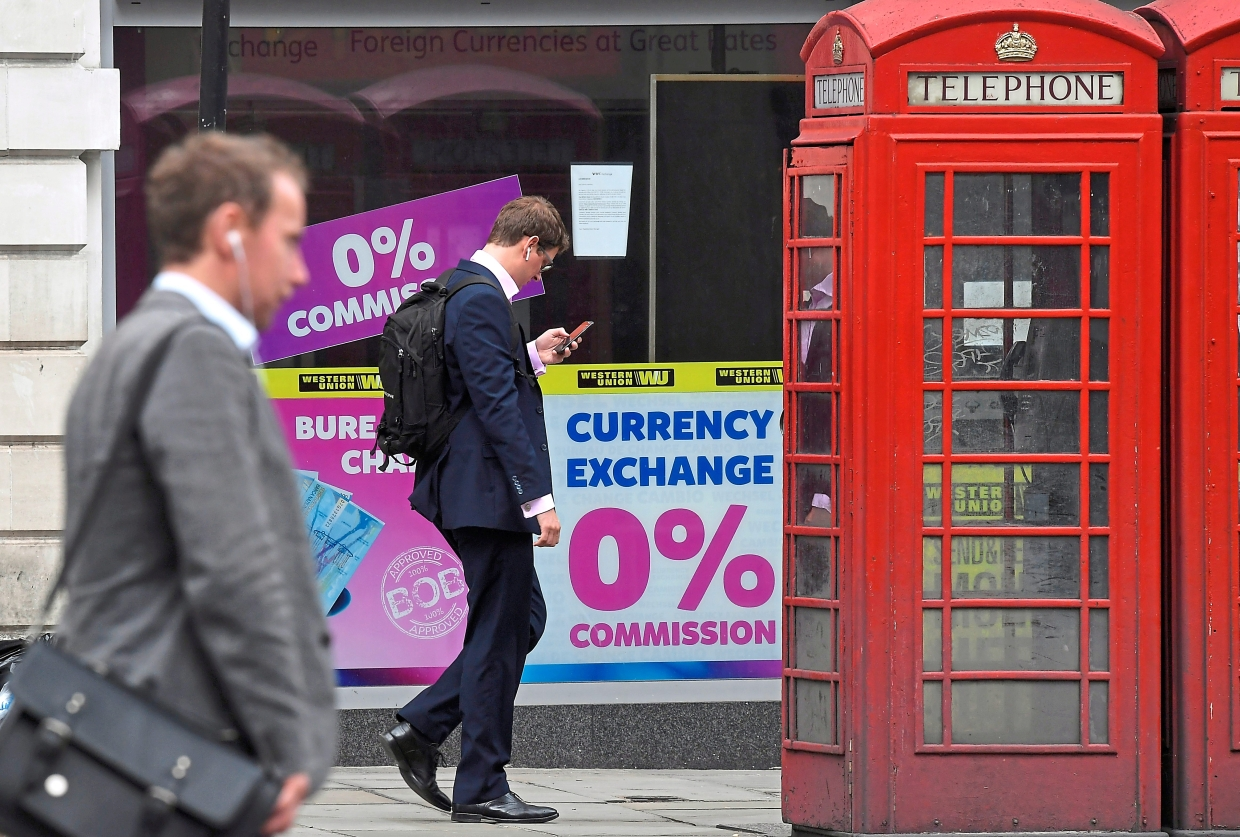 On downtrend: People walk past a currency exchange outlet in London. The pound has slid almost 7% since the UK deferred the original end-March Brexit deadline. — Reuters