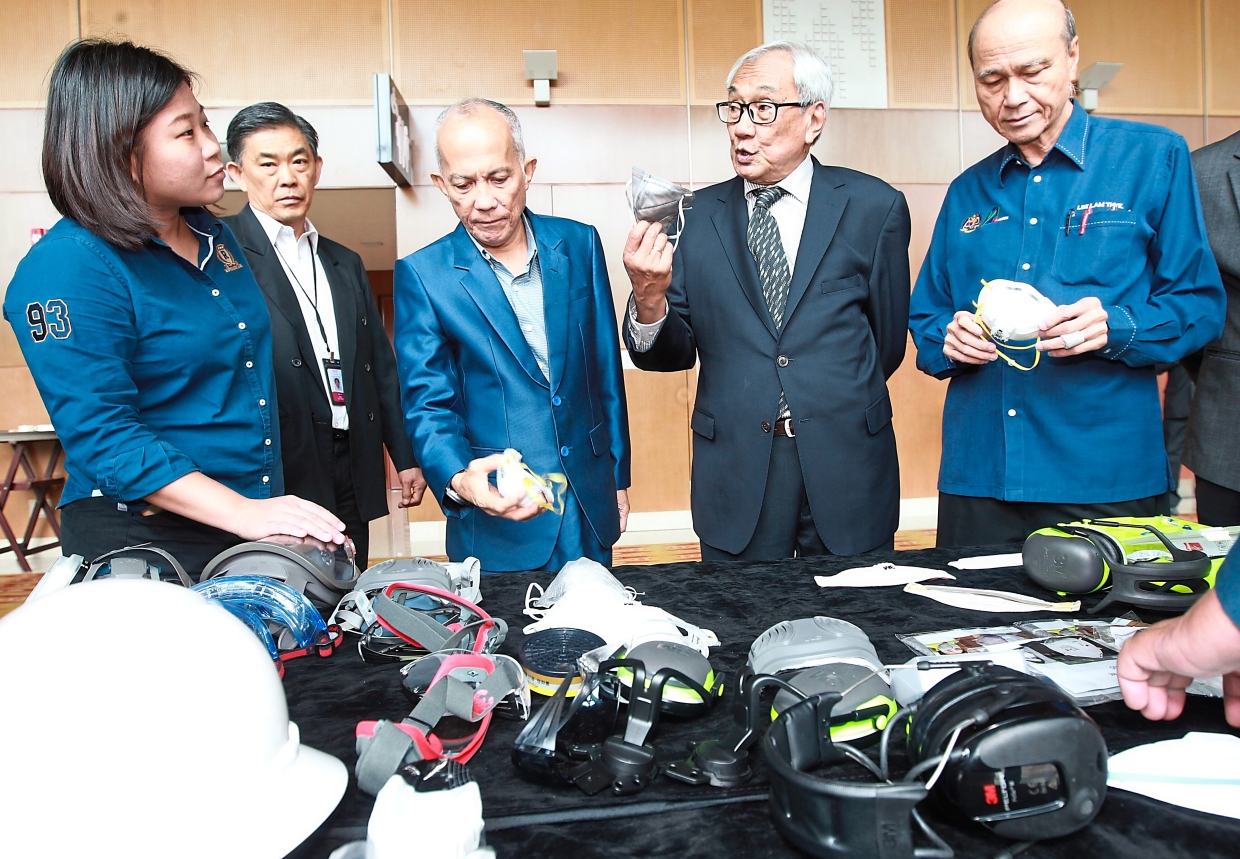 (From right) Lee, Astro Malaysia Holdings Bhd chairman Tun Zaki Azmi and Bernama chairman Datuk Seri Azman Ujang viewing some of the safety equipment on display at the  seminar.