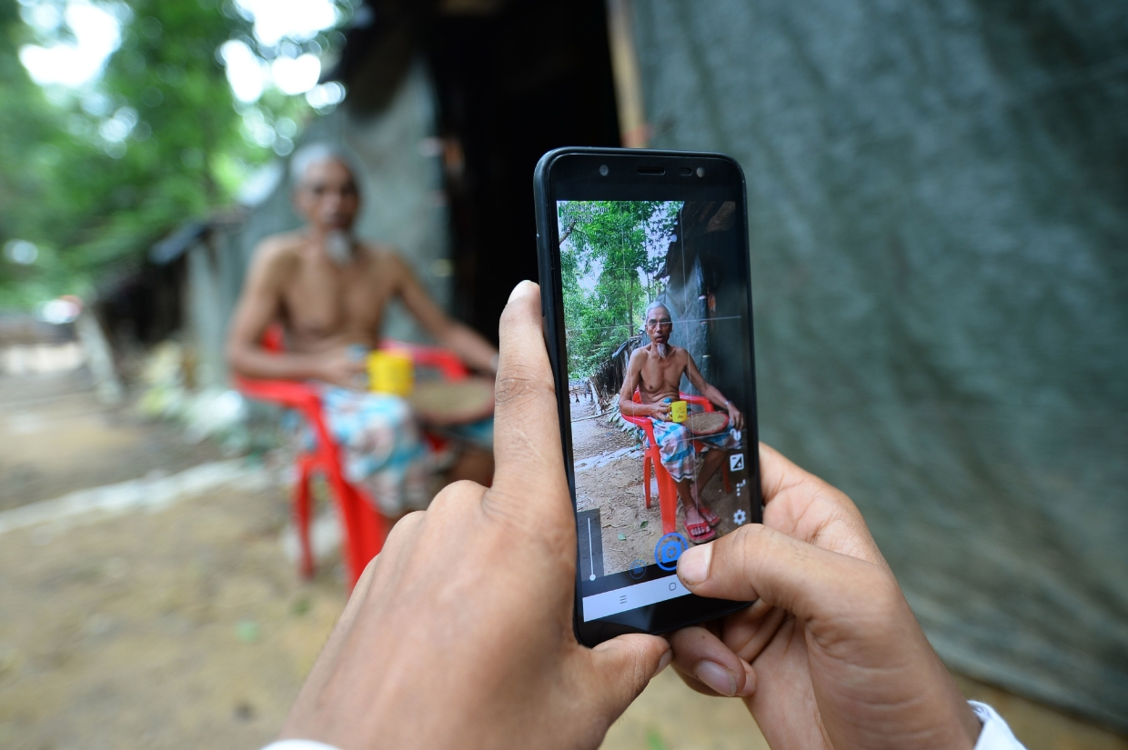 Rafiq using his mobile phone to take photos of a man by his shack at the Kutupalong refugee camp. — AFP