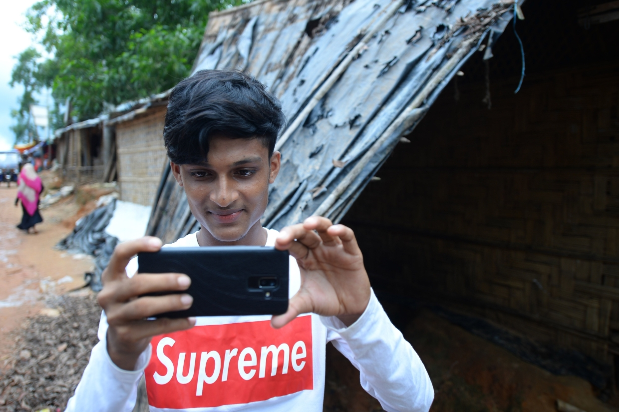 Rafiq, 19, one of 30 Rohingya youths selected by the World Food Programme for its 'Storytellers' project to record the daily lives of nearly one million stateless Rohingya in a vast camp in southern Bangladesh, shares the stories directly with the public through Facebook, Twitter and Instagram - showing to the outside world the raw, emotional ups and downs they face living in the world's largest refugee camp. — AFP