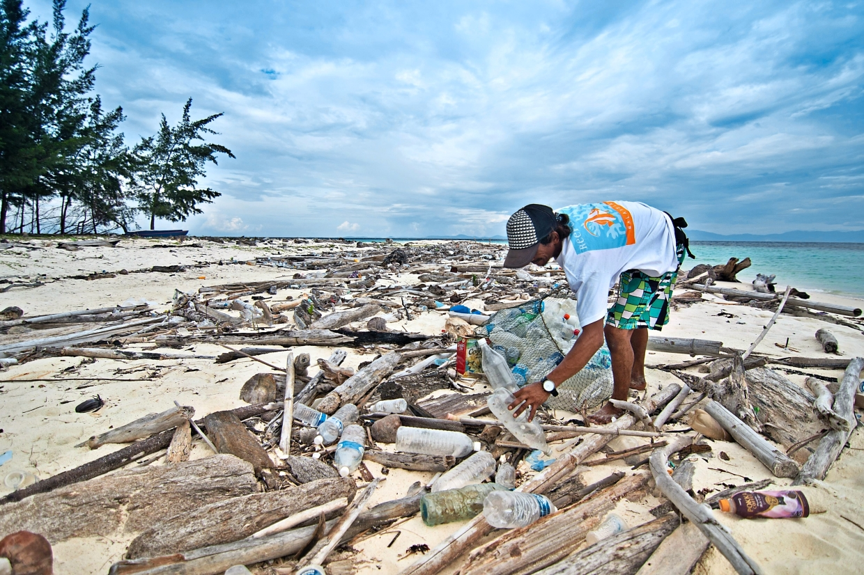 Reef Check Malaysia staff picking up plastic bottles at a beach in Mantanani Island, Sabah. —filepics