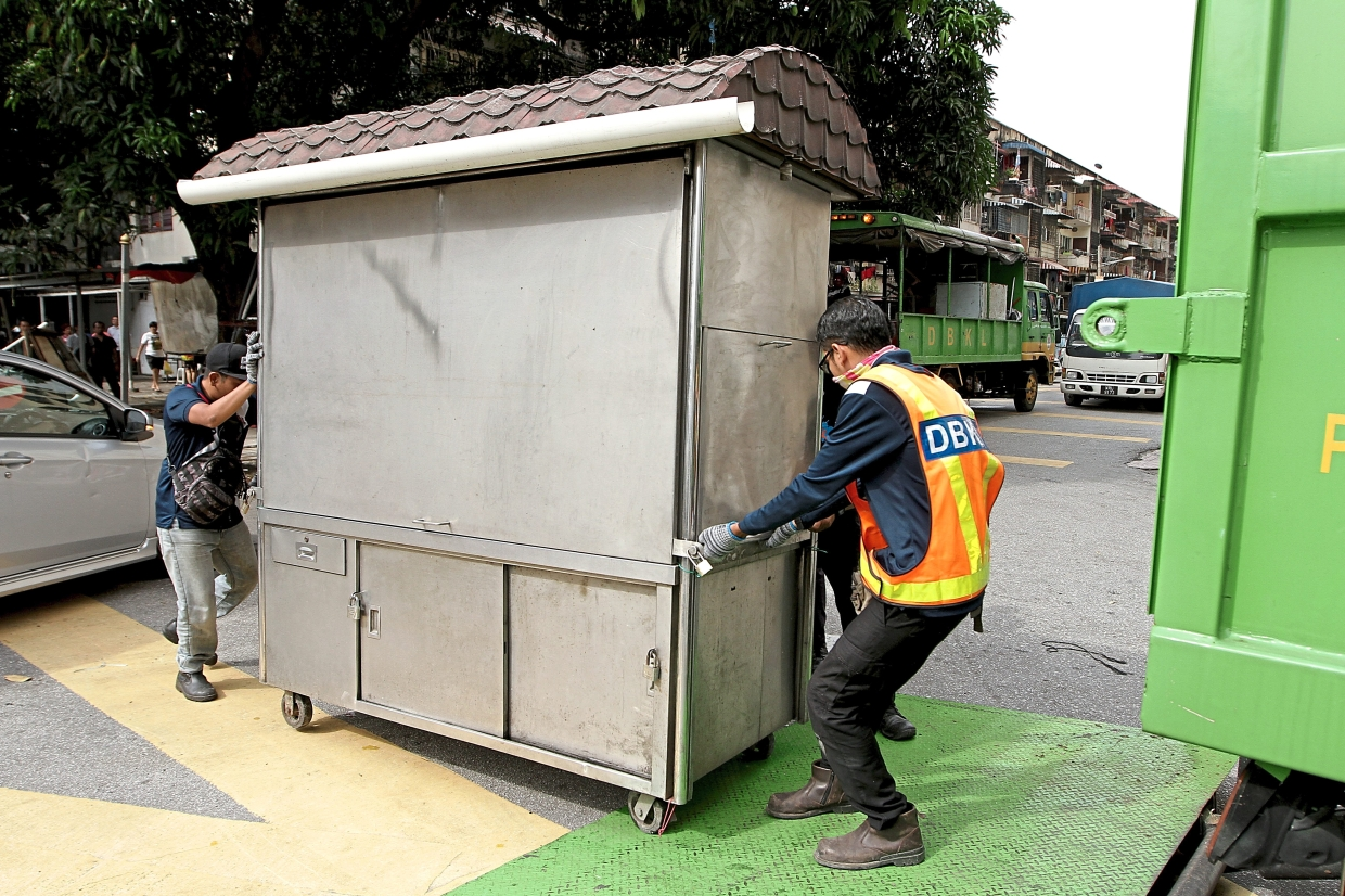 DBKL officers removing an illegal stall operating in Jalan Sepadu, off Jalan Kelang Lama. — Filepic