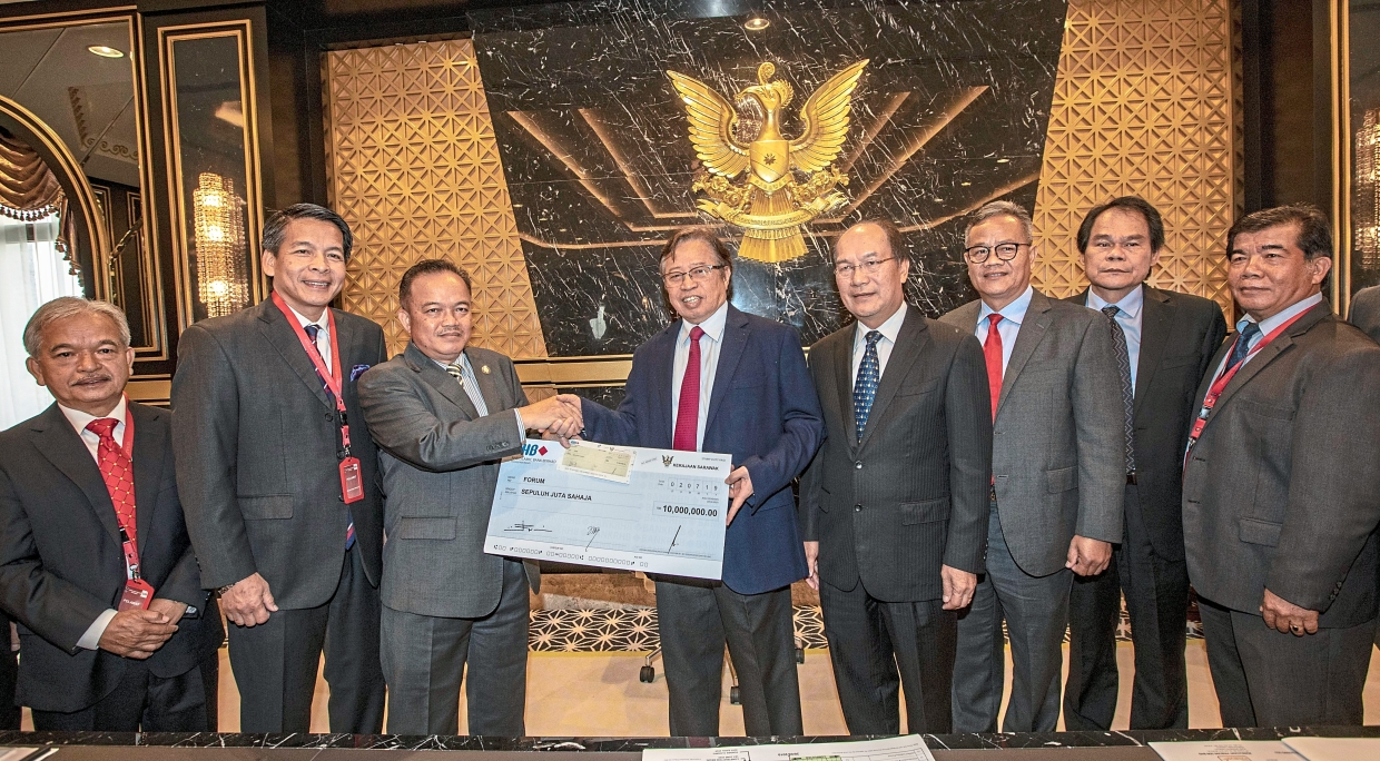Abang Johari (fourth from left) presenting the cheque to Forum president Antonio Kahti Galis, while Gerawat (fourth from right) and other Orang Ulu leaders look on.