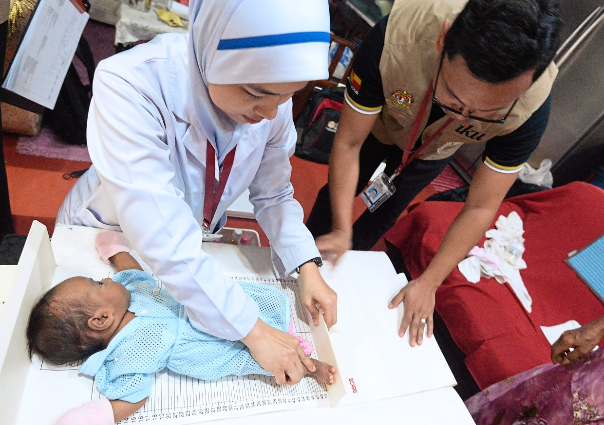 Nurse Nur Syakira Hazwani Mohamad Rudian (left)  and trained interviewer Syed Mohammad Iqbal Syed Mazlan checking the vital statistics of a baby in one of the houses visited during the national survey that involves about 12,000 households.