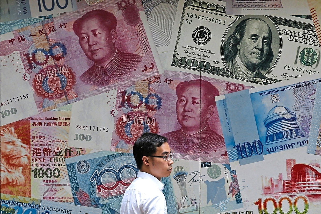 A man walks past a money exchange shop decorated with different banknotes at a business district in Hong Kong. Since the last meeting, the US dollar has strengthened as the global economic outlook dimmed, adding more downward pressure on prices by making imports cheaper. — AP