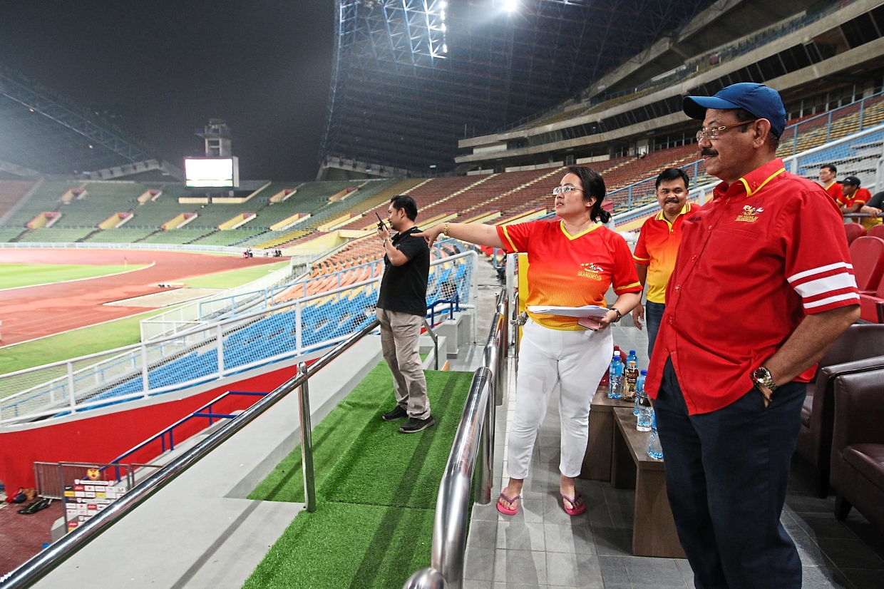 Abd Karim (right) and organising committee member Necia Abdullah (second from right) going through the details of tonight's opening ceremony during a rehearsal at the Shah Alam Stadium. — Photos: GLENN GUAN/The Star