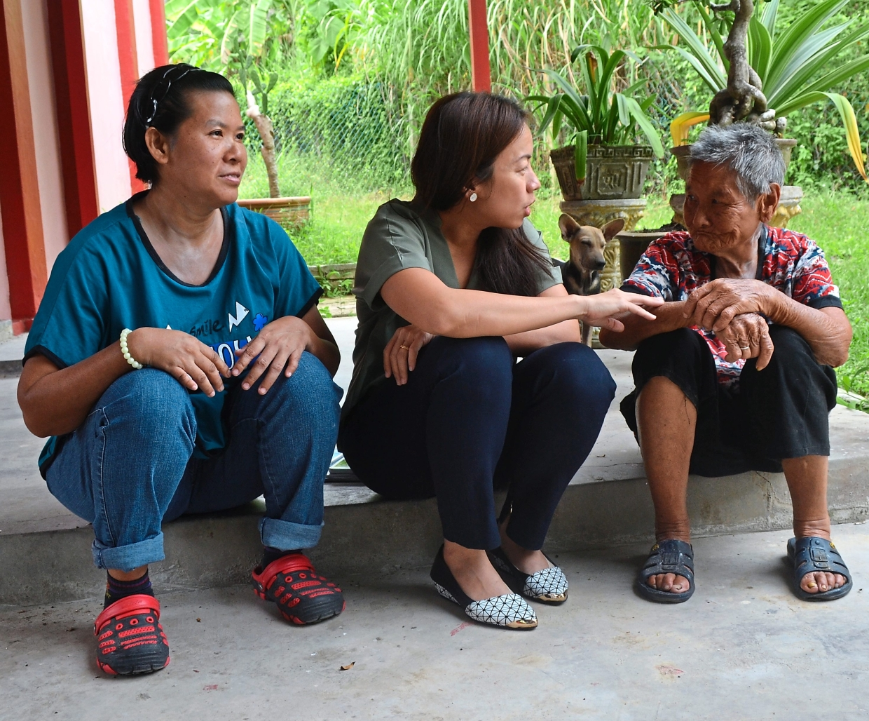 Heng (centre) assuring Chong that she would help send plumbers to deepen the bored well outside her house. With them is Ooi (left).