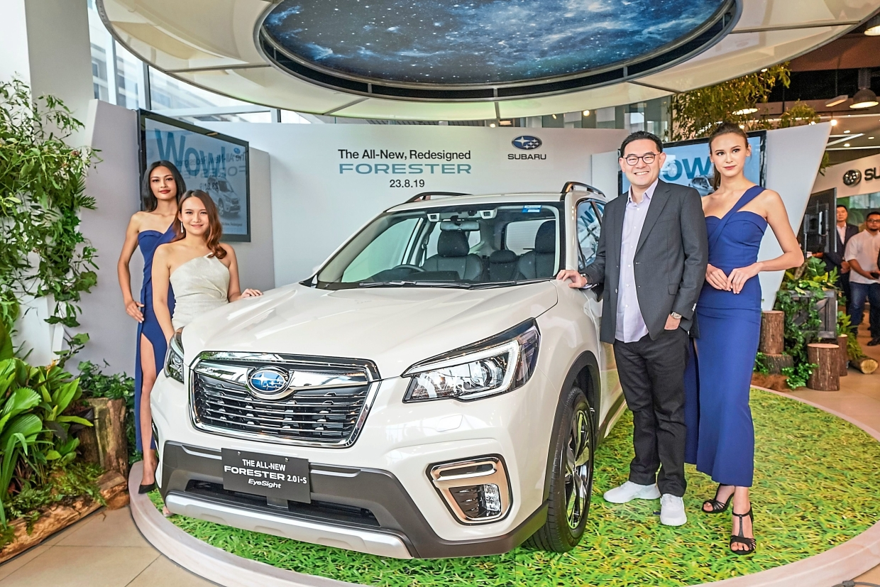 EyeSight technology: Tan posing with models at the launch of the Forester SUV. With EyeSight, the journey is safer and less stressful, according to Tan.