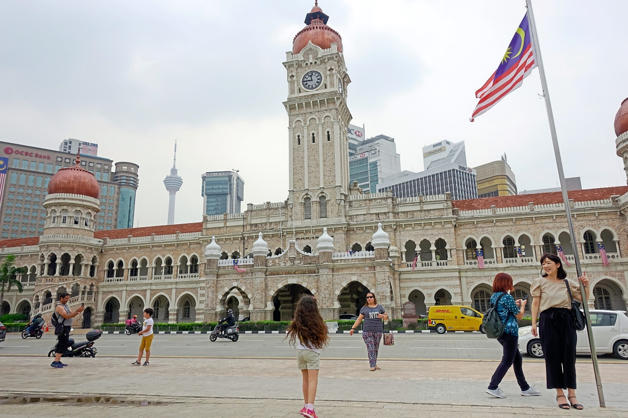Historical monument: Visitors posing with the clock and Sultan Abdul Samad building in the background.  —Bernama