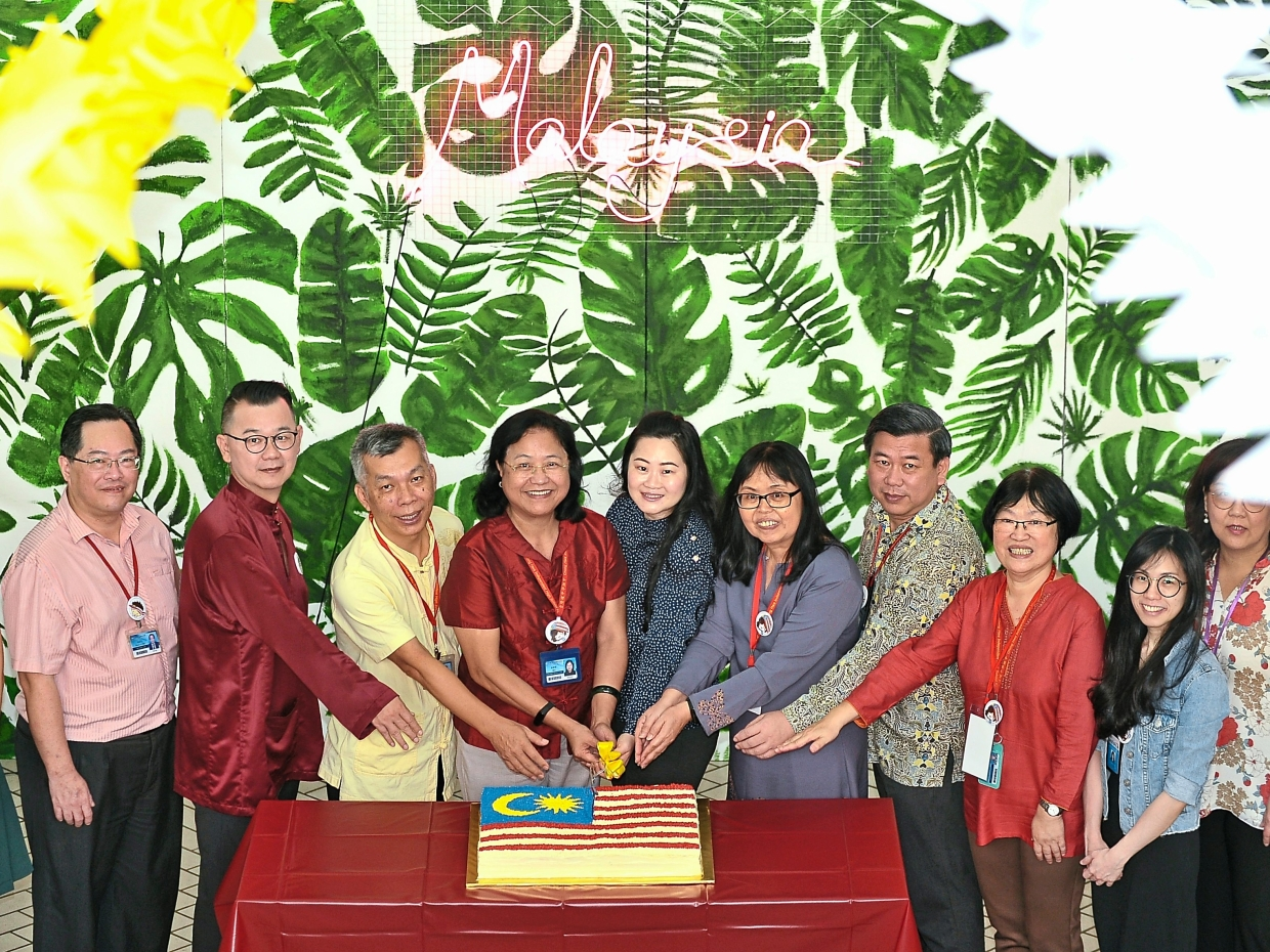 "Chong Hwa Independent High School principal Cheong (fourth left), staff and guests cutting a cake to mark its launch of the ""Raise The Flag"" campaign in conjunction with the school's national day celebrations."