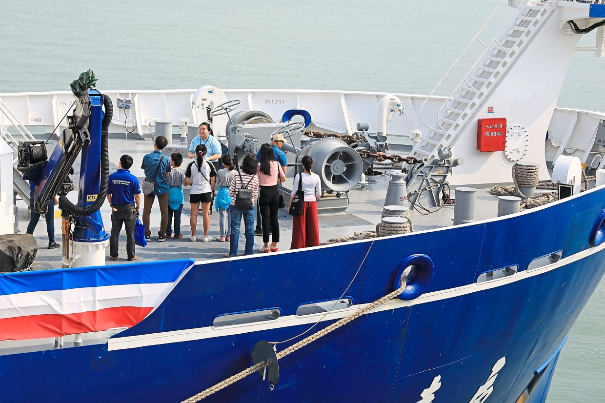 A student volunteer (in light blue) shows visitors around the research vessel.