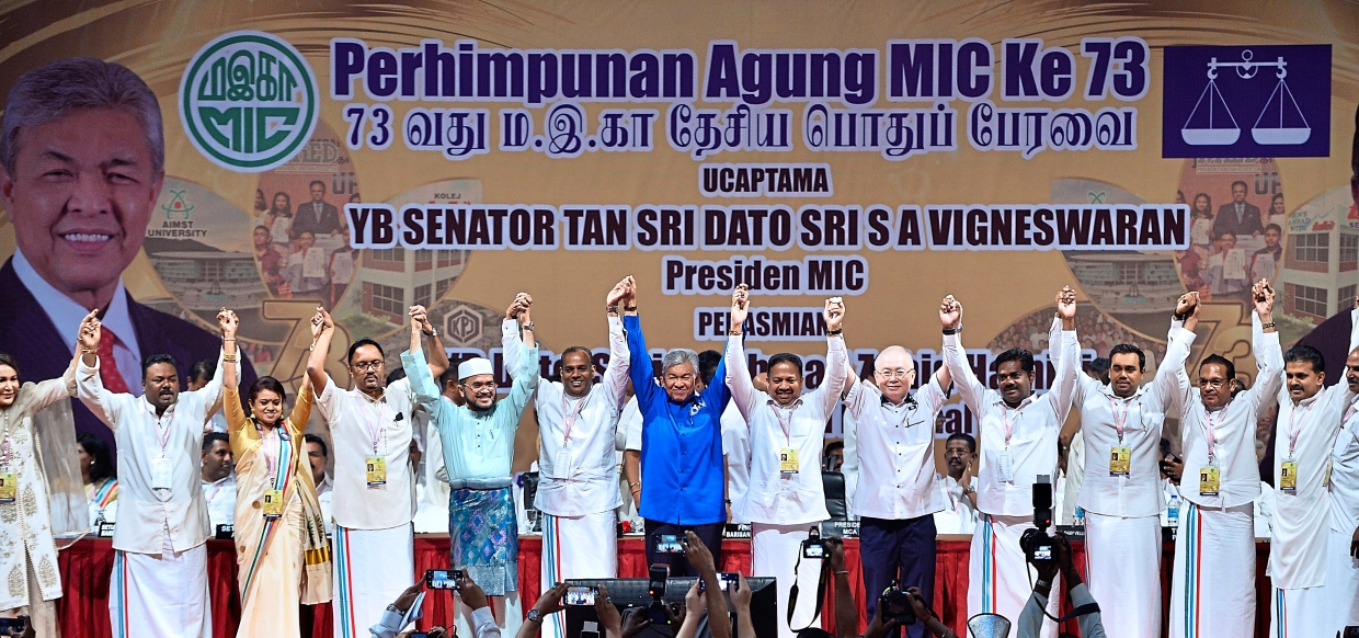 Hands joined in unity: Ahmad Zahid officiates the MIC 73rd annual general assembly together with Vigneswaran and Dr Wee  at the Putra World Trade Centre.