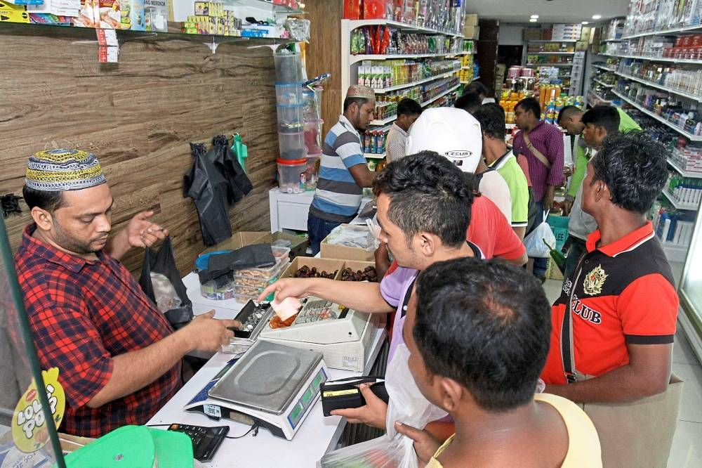 Foreigners shopping at a supermart manned by fellow foreigners  in a shop in George Town.