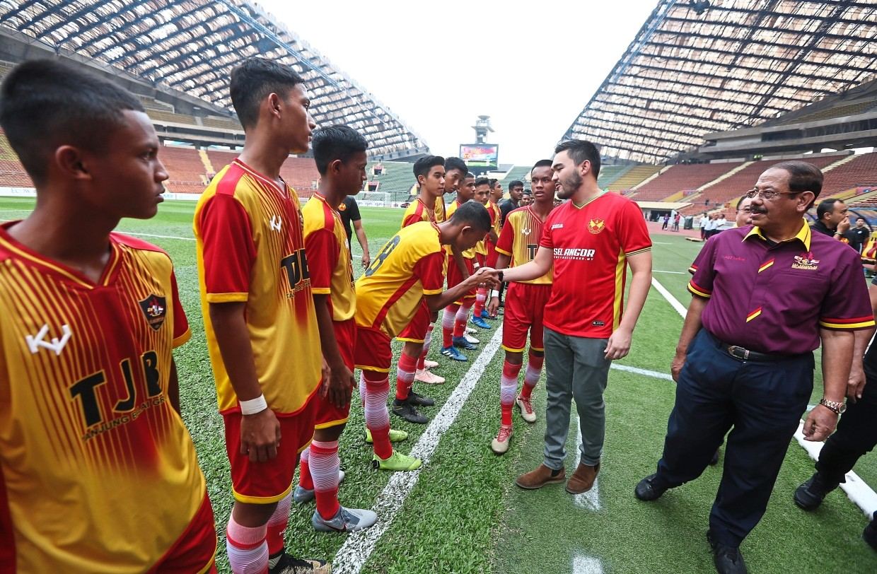 Tengku Amir Shah (right) shaking hands with the Selangor Under-15 players before their match.