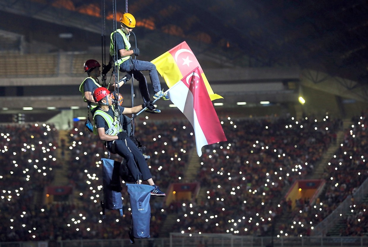 Three abseiling stuntman bringing down the Selangor and Singapore flags for the opening ceremony at Shah Alam Stadium.