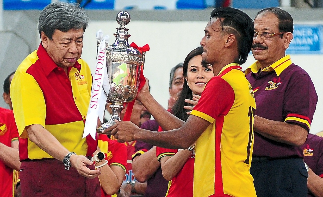 Sultan Sharafuddin (left) presenting the champions trophy to Amri (second from right) after the home side edged Singapore 1-0. Looking on are Abd Karim (right) and Tengku Permaisuri Norashikin. — Bernama
