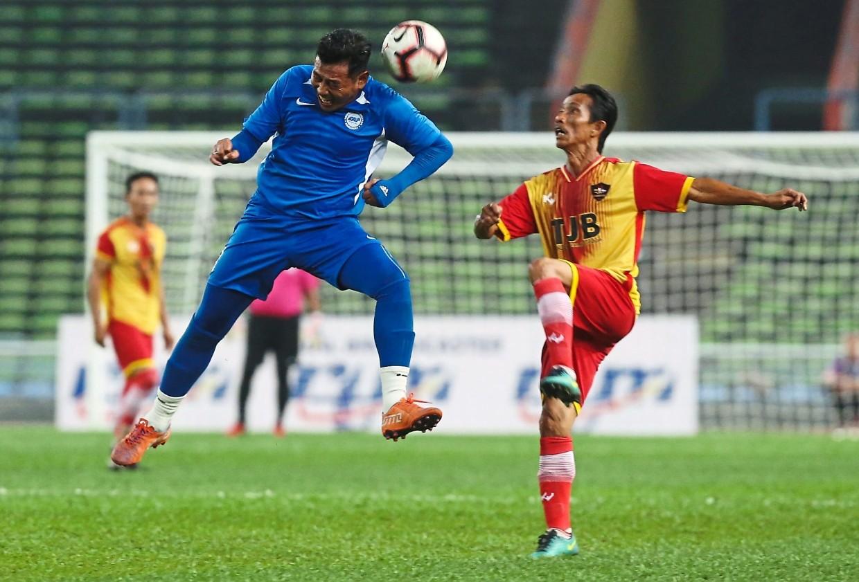 Singapore veteran Nahar Daud (left) heading the ball away from Selangor's Zainal Nordin during the curtain raiser.