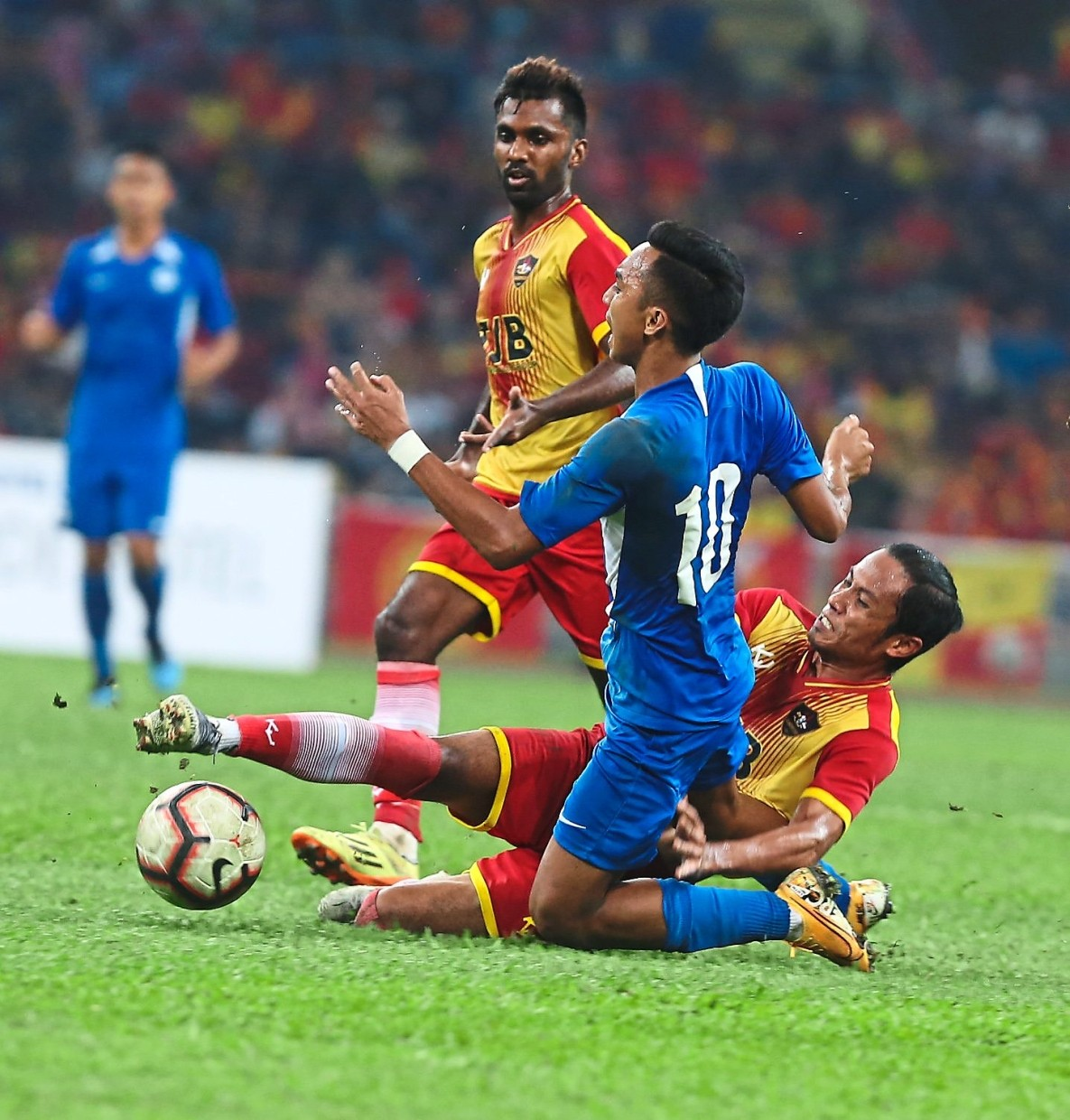 Singapore Selection's Mohd Faris Ramli (in blue) being tackled by Selangor's Khyril Muhymeen Zamri (on the ground) during the match.