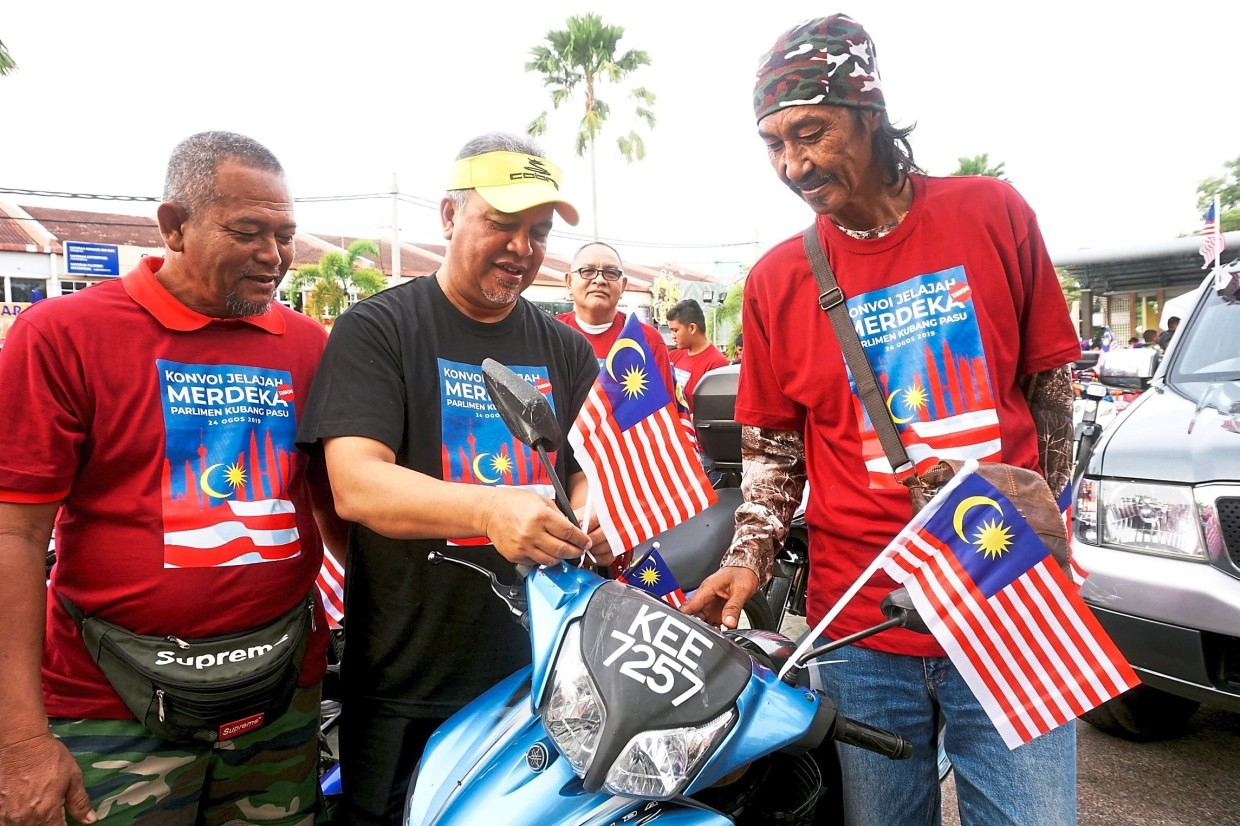 Amiruddin (centre) affixing a mini Jalur Gemilang on the motorcycle of a convoy participant.