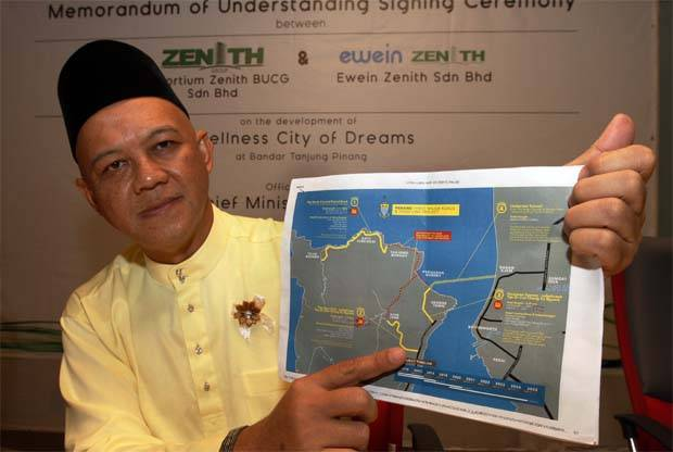 In this Star file pic taken on Aug 13 2015, Consortium Zenith BUCG official Datuk Zarul Ahmad Zulkifli shows an illustration of the roads and undersea tunnel that the consortium will build in Penang .