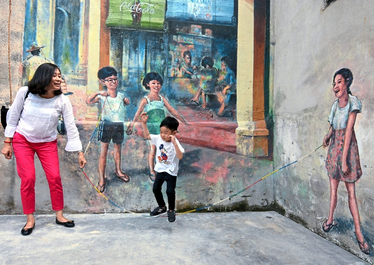 A woman playing a game with her son beside a mural along Lorong Panggung and Jalan Petaling in Chinatown.