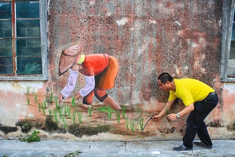 Sekinchan assemblyman Ng Suee Lim posing with the murals at Jalan Radin in Sekinchan.