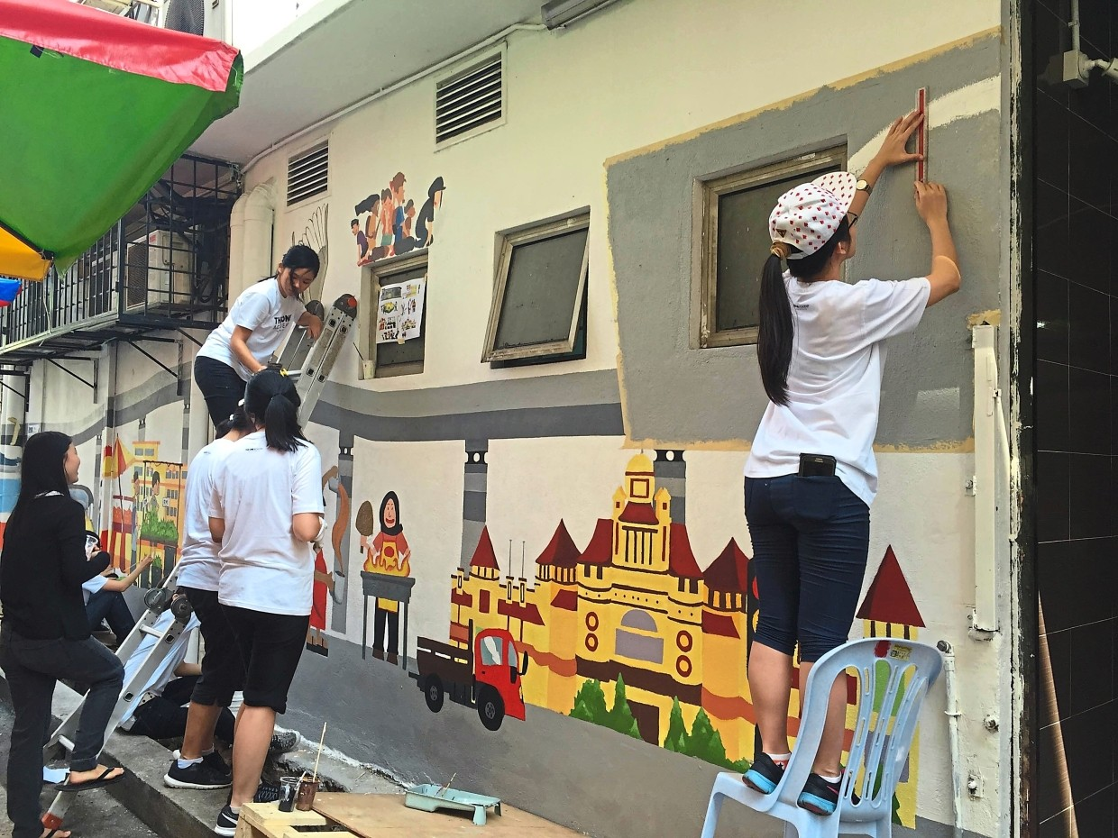 Students hard at work completing two murals on the backlane of Jalan Kenari 5.