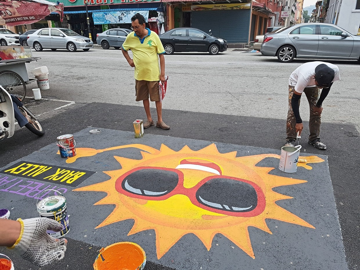 A curious passer-by observing the artists painting  a cheerful road design.